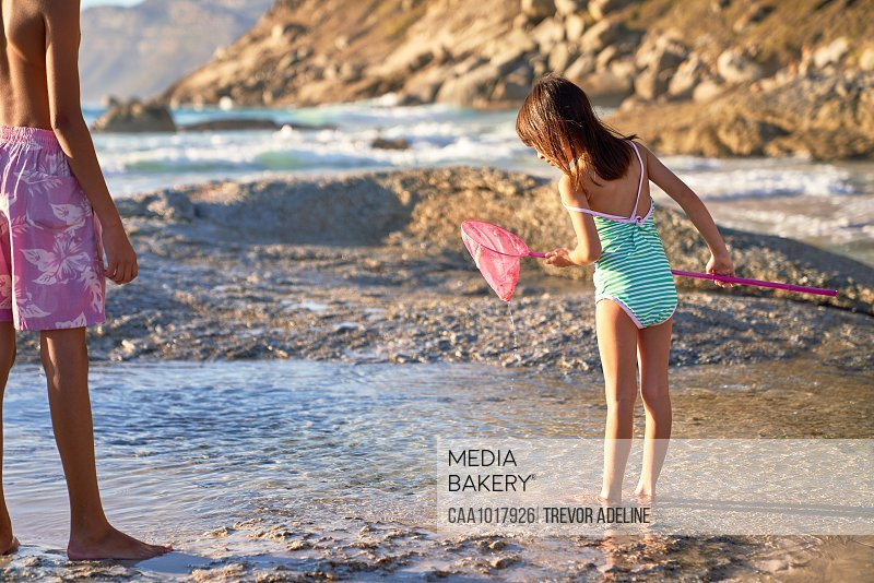 Girl with fishing net playing in tide pool on sunny beach