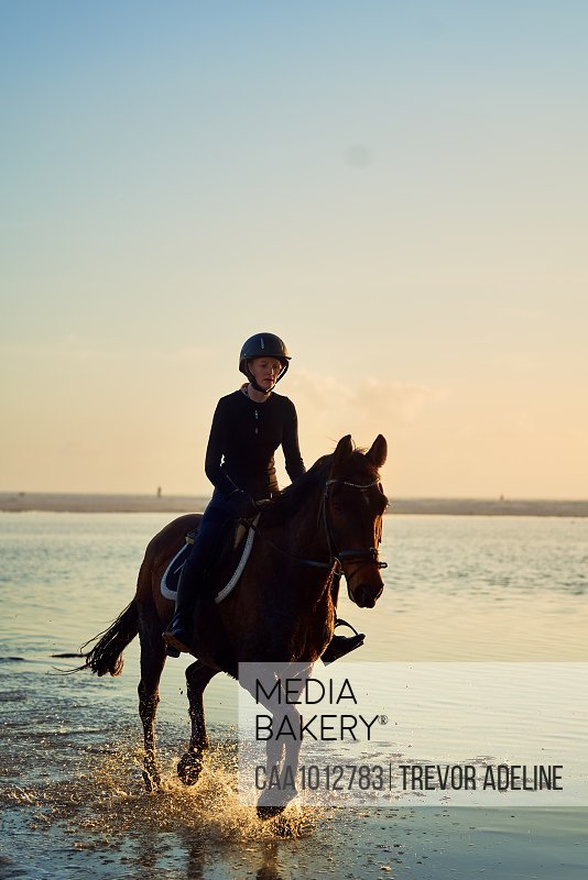 Young woman horseback riding in ocean surf