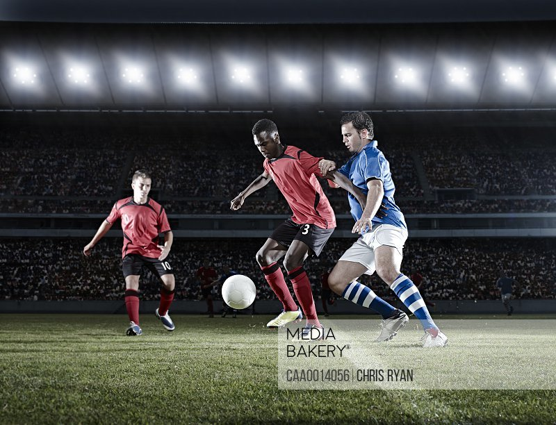 Soccer players with ball on field