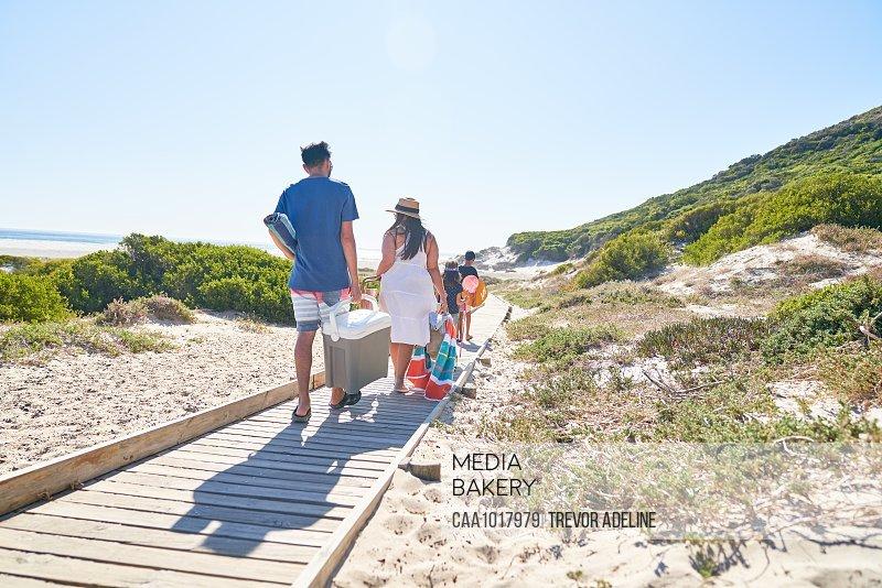 Family carrying equipment on sunny beach boardwalk