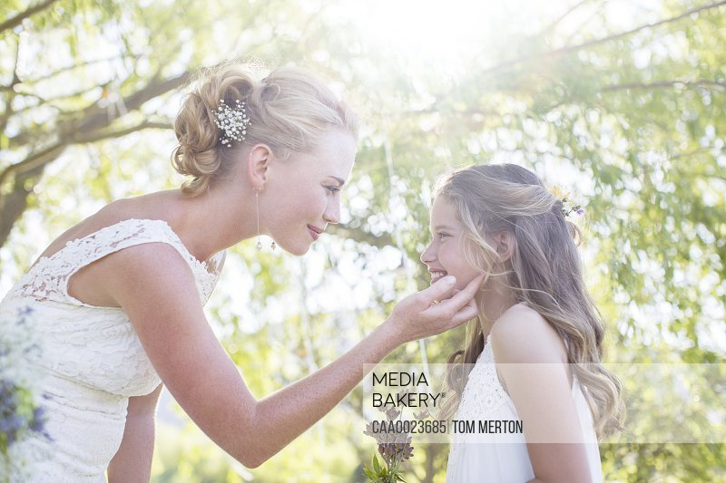 Bride and bridesmaid facing each other in domestic garden during wedding reception