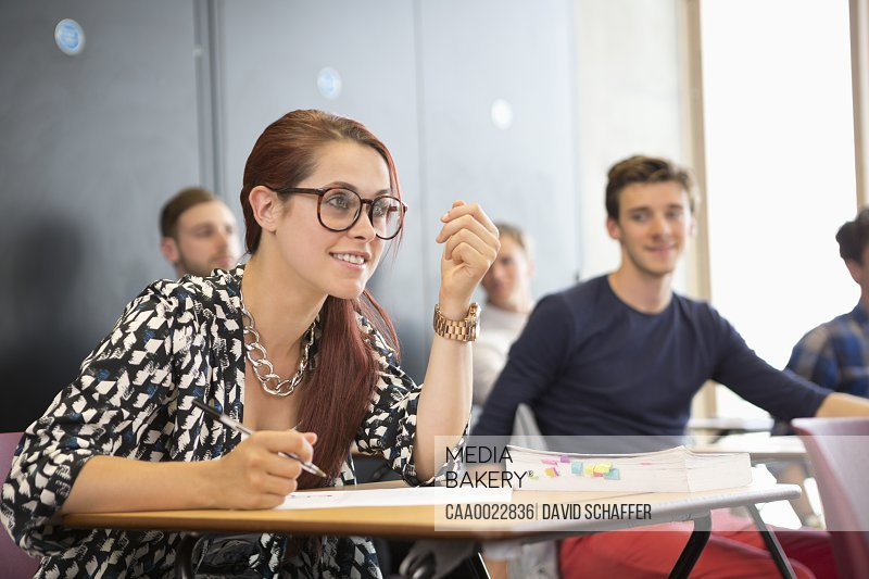 University student taking notes and listening during seminar in classroom