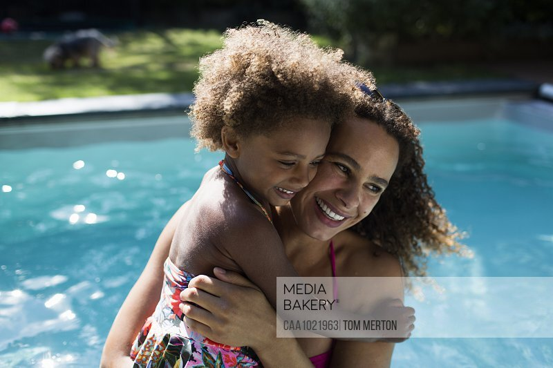 Happy mother and daughter hugging at sunny summer poolside