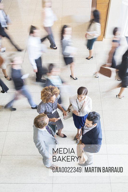High angle view of Business people standing in office talking and smiling