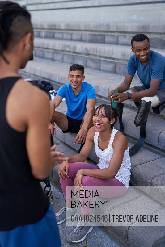 Happy athletes talking on steps