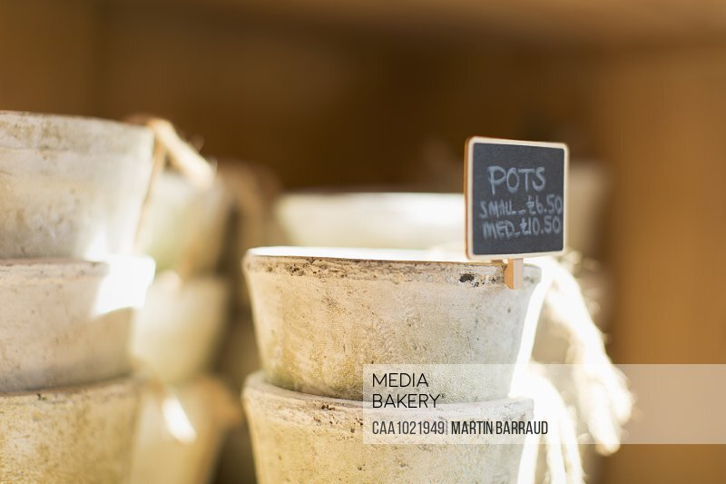 Close up flowerpots with sign stacked in plant nursery