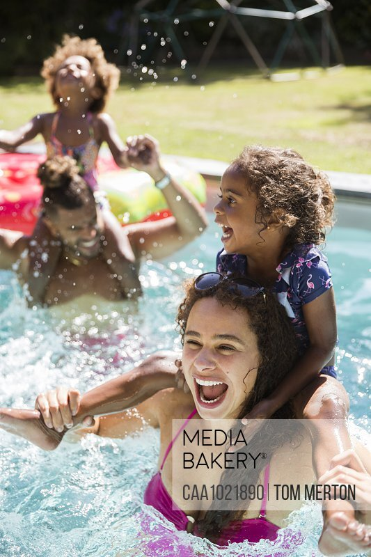 Happy playful family in sunny summer swimming pool