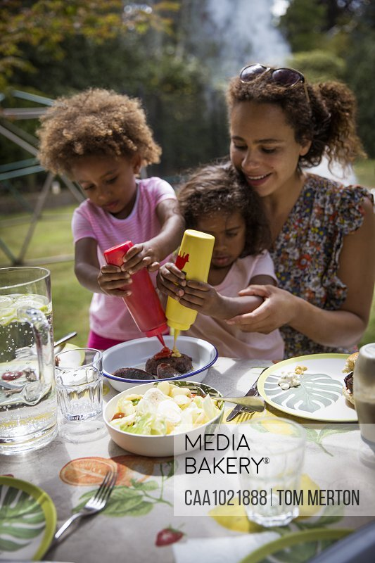 Mother and daughters enjoying summer backyard barbecue at table