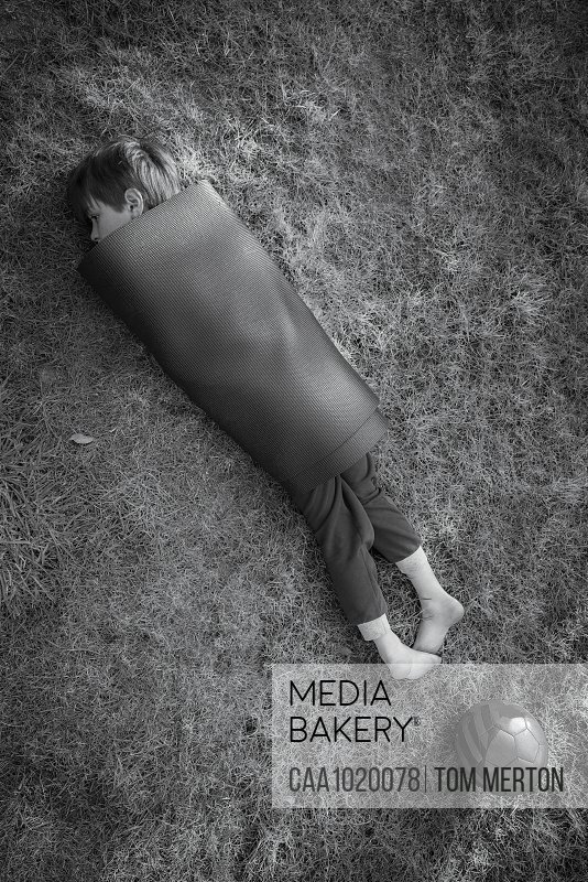 Boy wrapped in yoga mat in grass