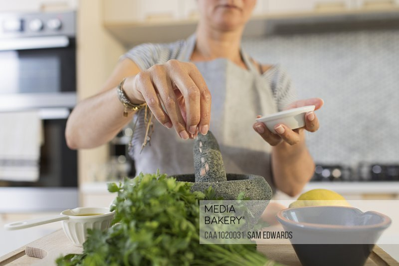 Woman cooking with mortar and pestle in kitchen