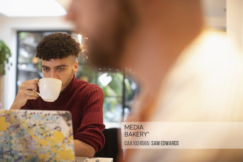 Young man drinking coffee working from home at laptop
