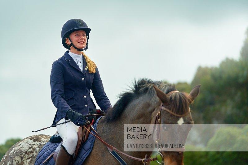Confident smiling teenage girl equestrian horseback riding