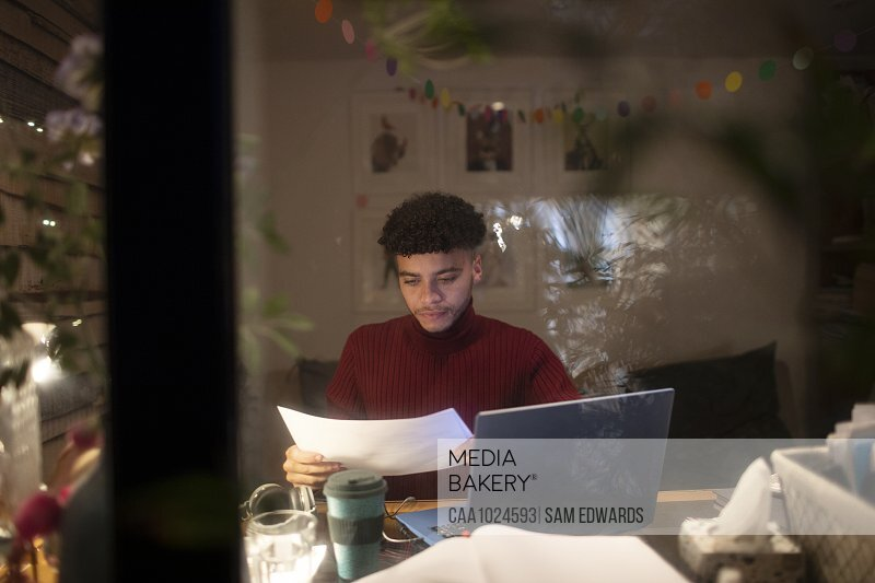 Focused young man with paperwork working from home at laptop at night