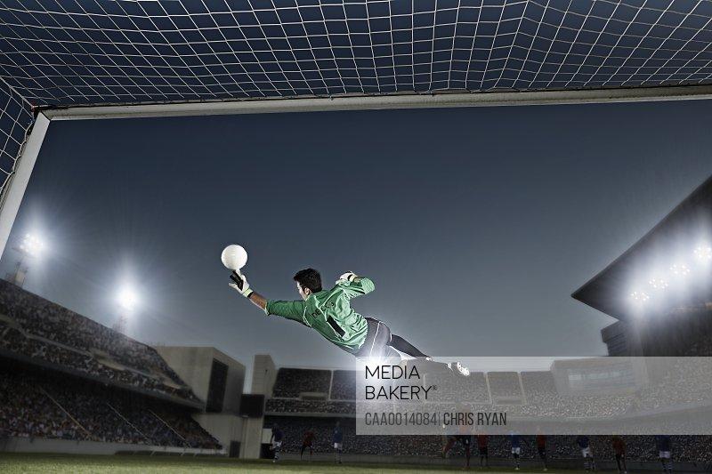 Goalie jumping for ball in soccer net