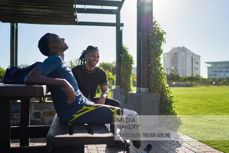 Male amputee athlete and trainer on sunny park bench