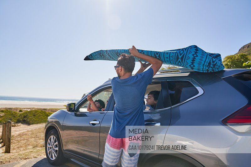 Man removing surfboard from top of car in beach parking lot