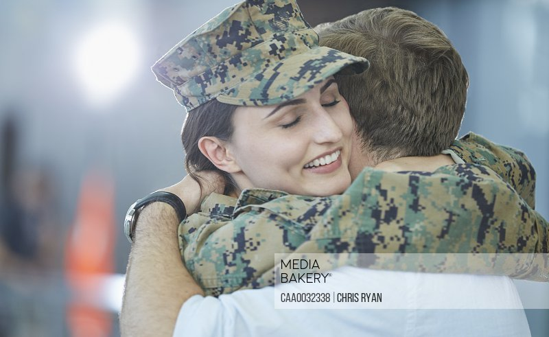 Husband greeting hugging soldier wife