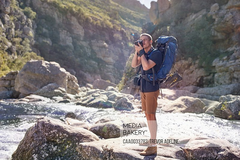 Young man with backpack hiking photographing with camera on sunny rocks