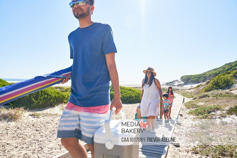 Family carrying beach equipment on sunny boardwalk