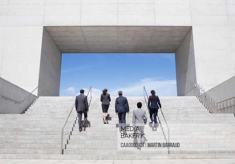 Business people ascending modern stairs