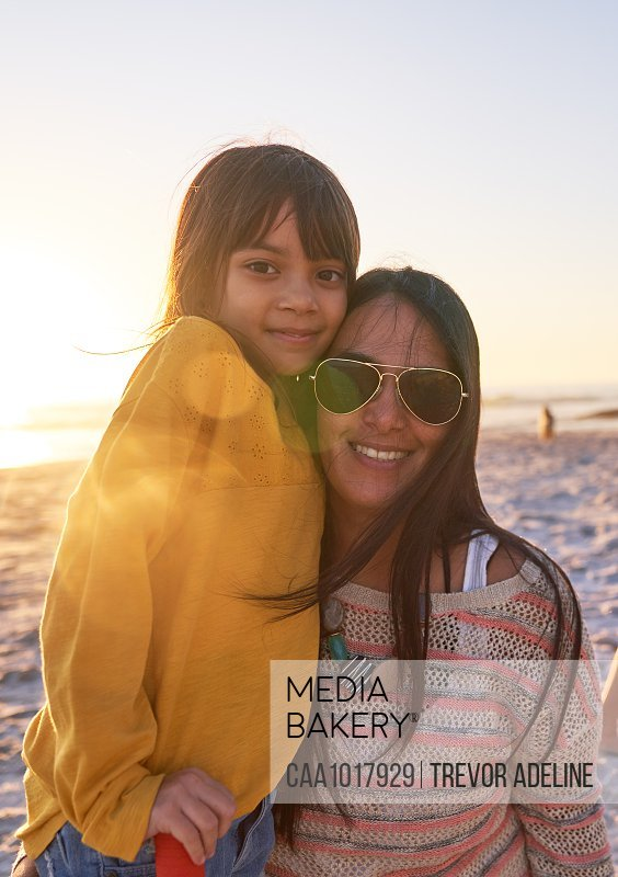 Portrait happy mother and daughter on sunny beach at sunset