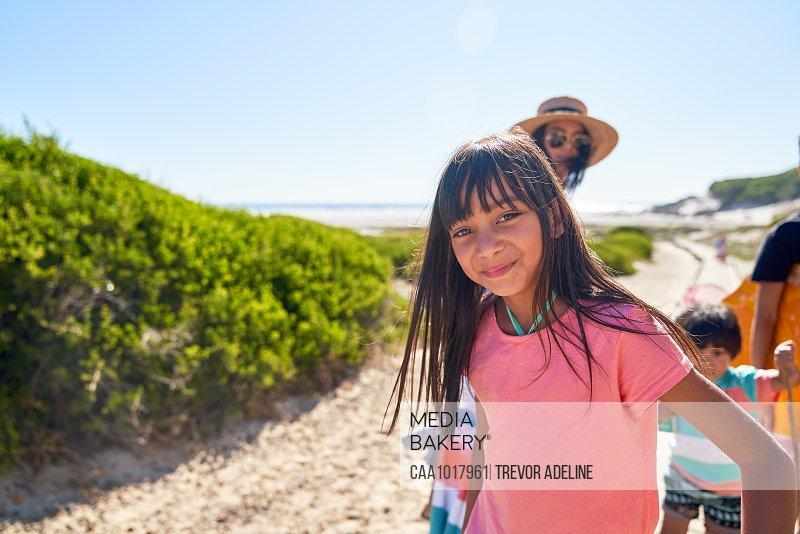 Portrait happy girl on sunny beach with family