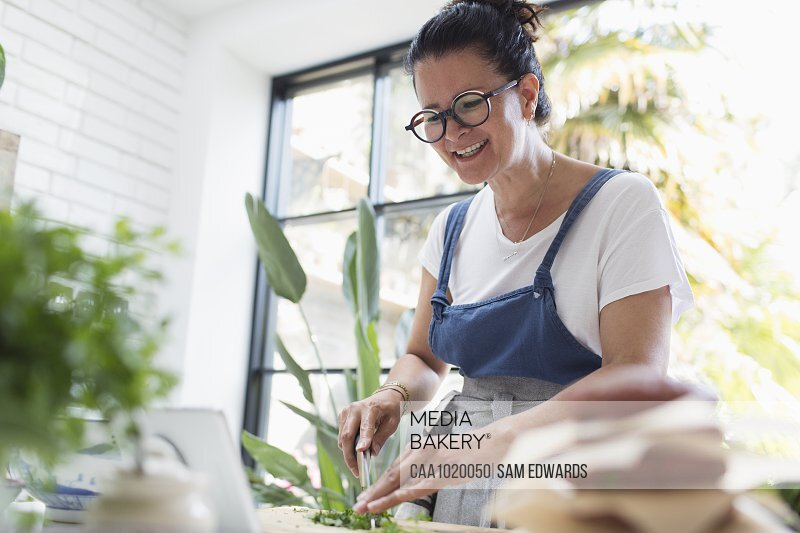 Smiling woman cooking at digital tablet in kitchen