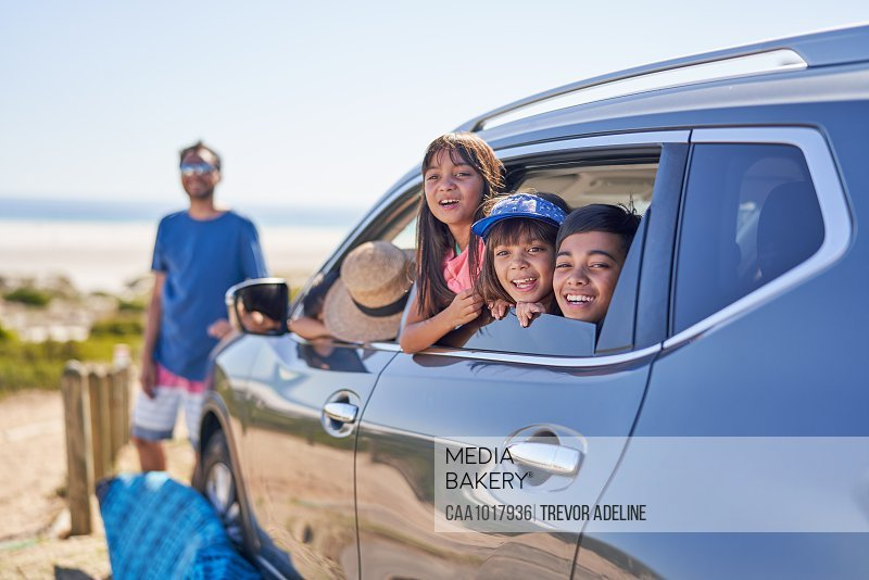 Portrait happy family in car at sunny  beach