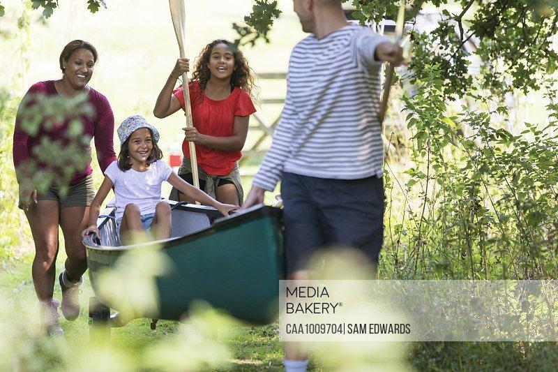Family pulling canoe in woods