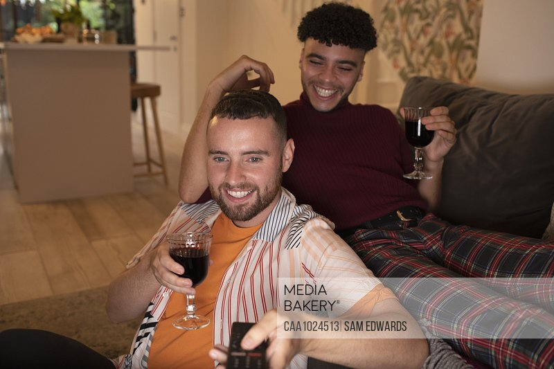 Happy gay male couple drinking wine and watching TV on sofa
