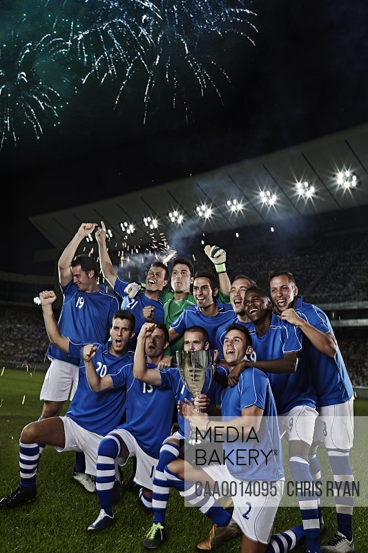 Soccer team cheering with trophy on field