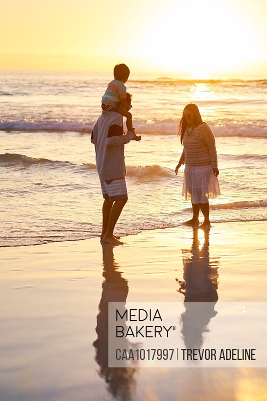 Family wading in ocean surf at sunset