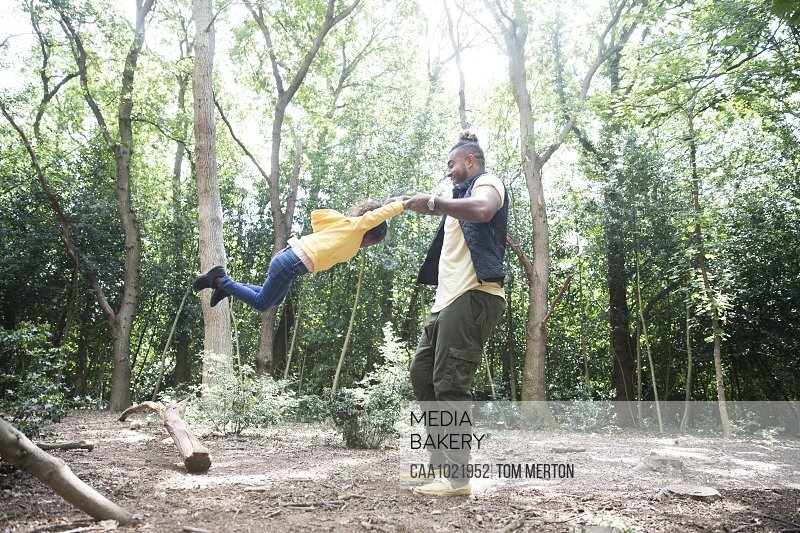 Playful father swinging daughter below trees in sunny woods