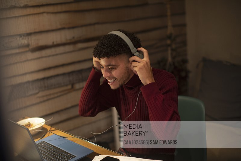 Happy young man with headphones working from home at laptop