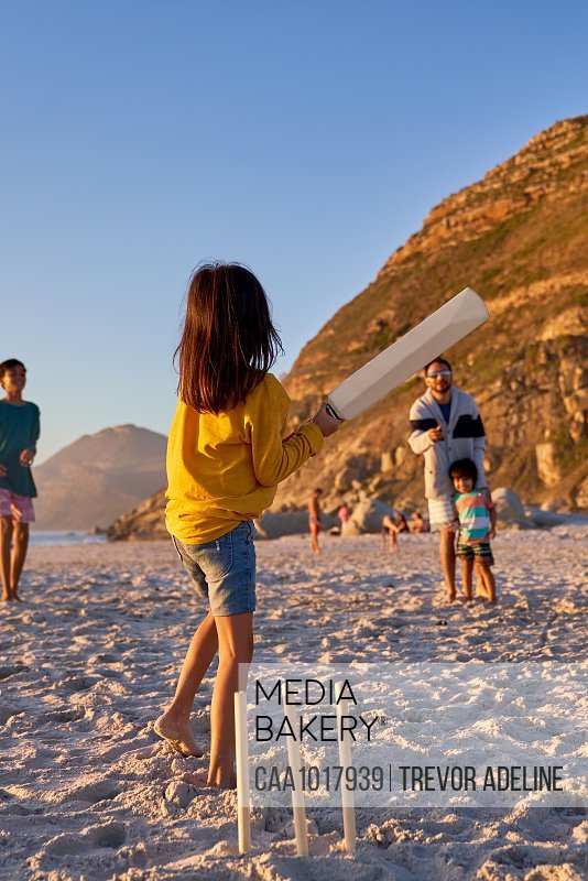Family playing cricket on summer beach