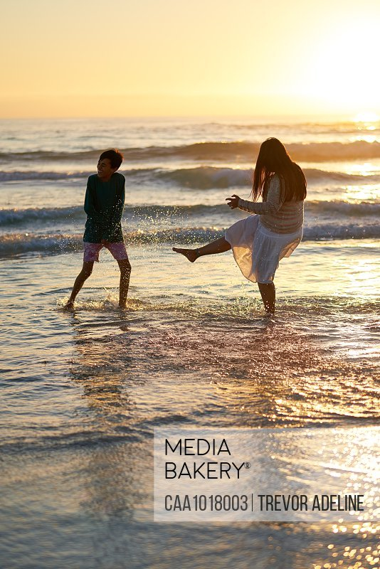 Happy mother and son splashing in ocean surf at sunset