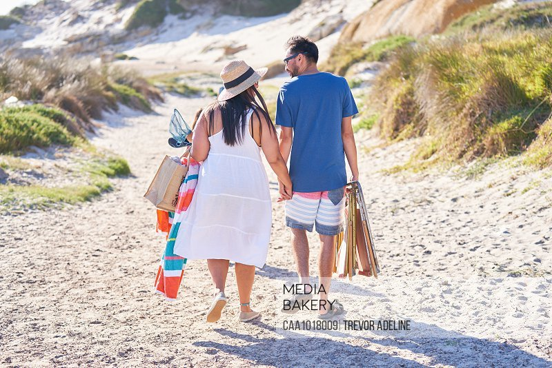 Affectionate couple walking on sunny beach path