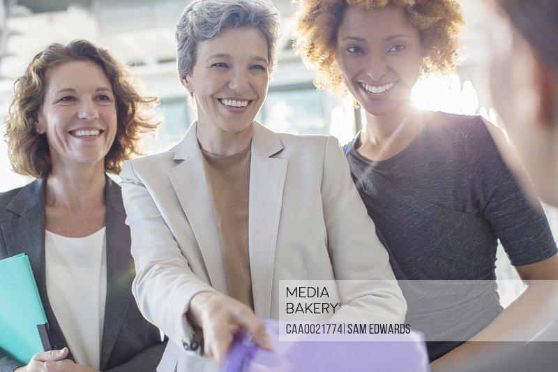 Three smiling businesswomen holding documents
