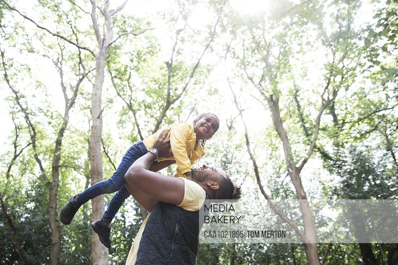 Playful carefree father lifting daughter below trees in sunny park