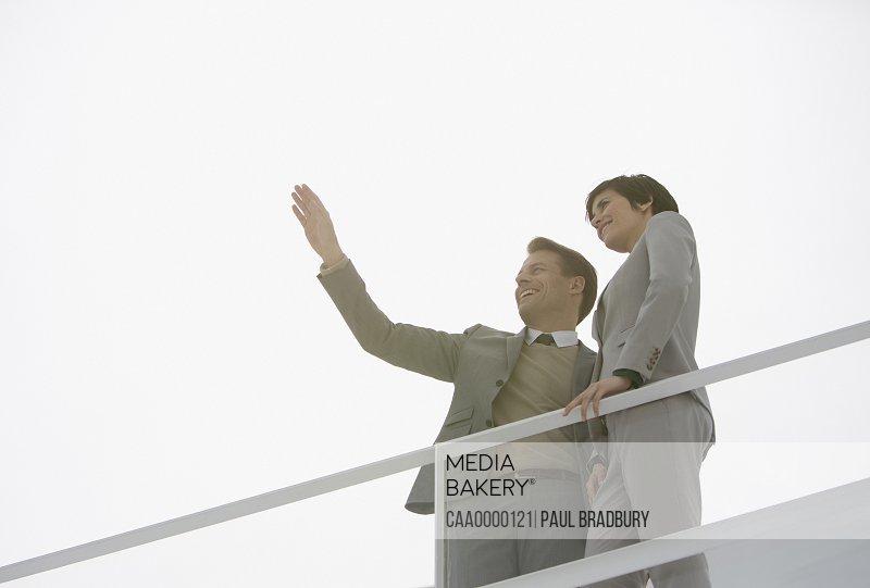 Sun shining behind gesturing businessman and businesswoman
