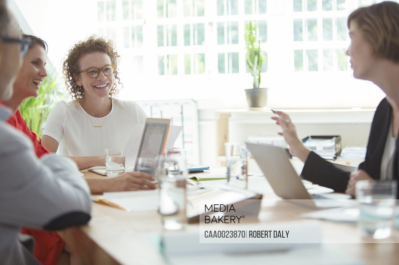 People talking and smiling during business meeting in office