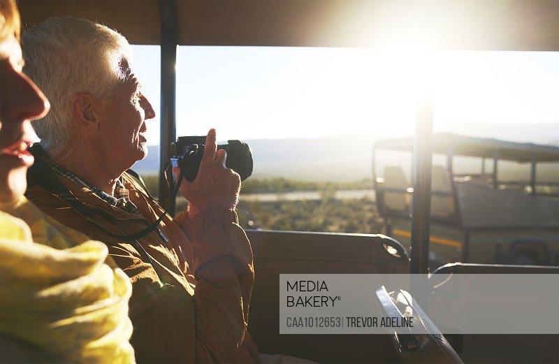 Senior couple with digital camera riding in safari off-road vehicle