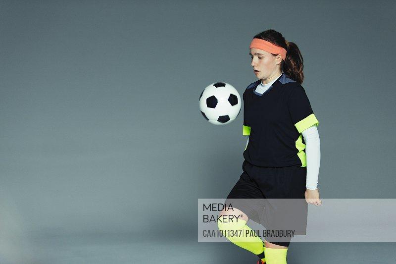 Teenage girl soccer player bouncing ball on knee