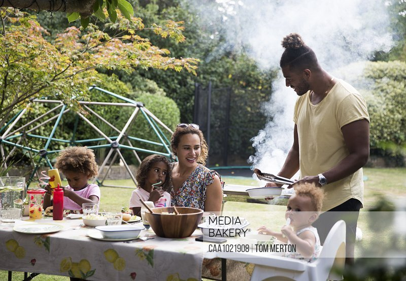 Happy family enjoying summer barbecue at patio table