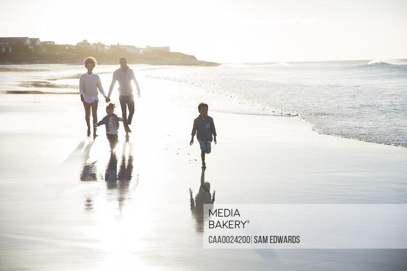 Family walking on beach at sunset