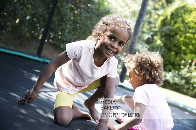 Portrait carefree sisters playing on backyard trampoline