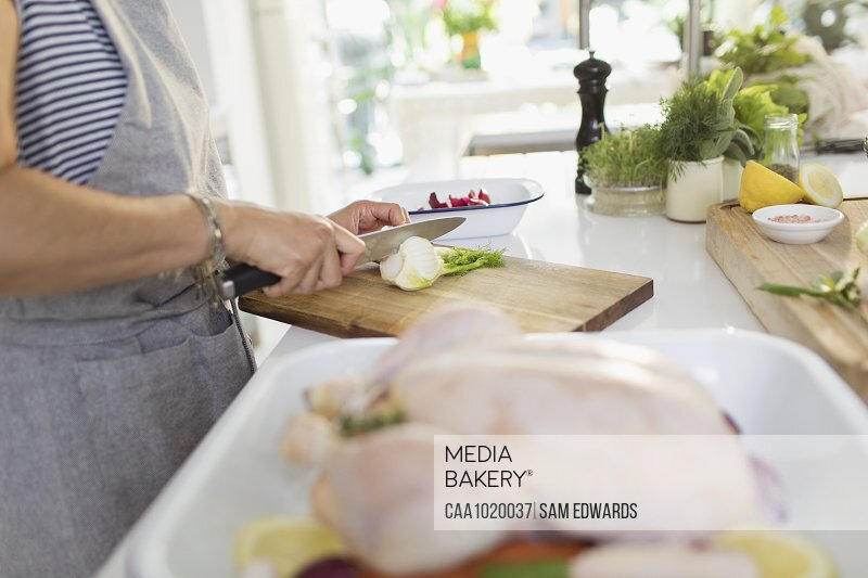 Woman cutting herbs for chicken dish in kitchen