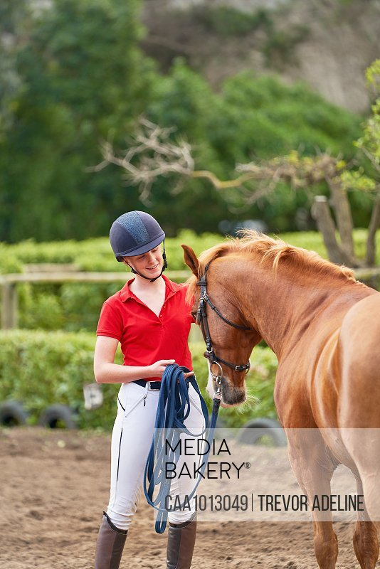 Teenage girl in equestrian helmet training horse