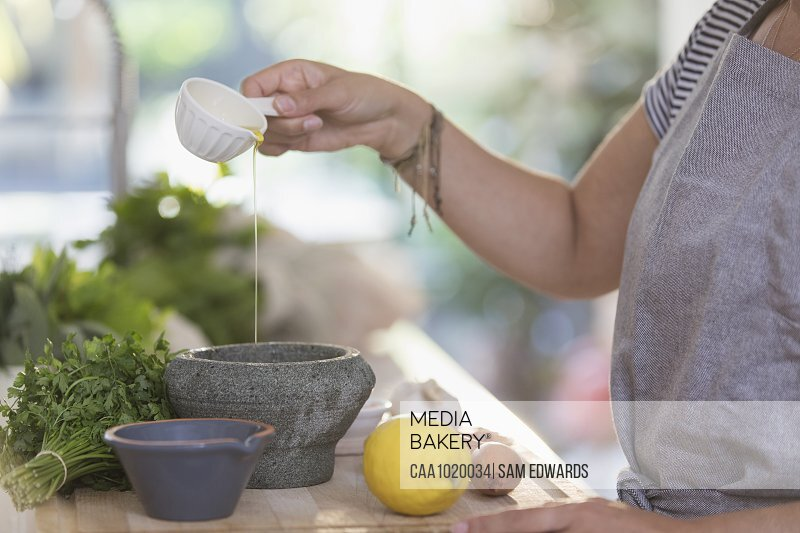 Woman cooking with olive oil and mortar in kitchen