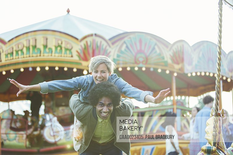 Portrait of young multiracial couple having fun in amusement park